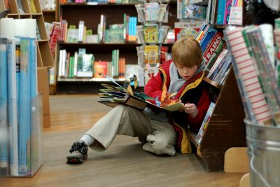 Young book wyrm reading book in bookstore